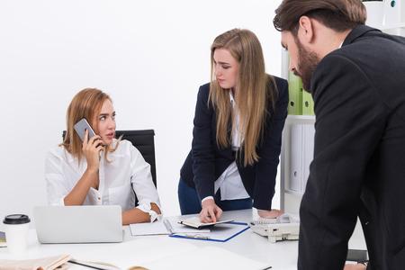 Bedrijfs dame is op haar telefoon. Zowel zakenman en zakenvrouw op zoek naar haar en wachten op de uitkomst. Concept belangrijke telefoongesprek