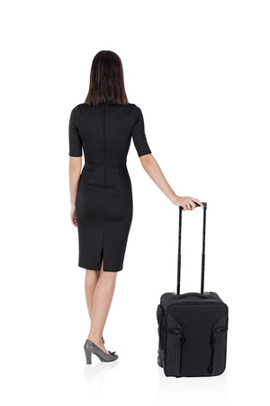 dragging: Isolated rear view of woman in business suit with suitcase standing with her back to the viewer. Concept of travelling. Mock up Stock Photo