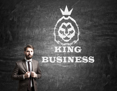 professionalism: Serious bearded man in suit is standing near blackboard with king of business sketch on it. Concept of professionalism Stock Photo