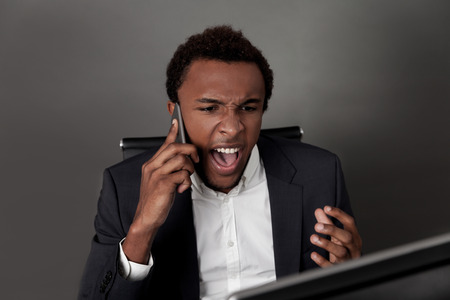 telephone cord: Angry African American businessman is shouting at his colleague at the second end of telephone cord. Concept of anger management