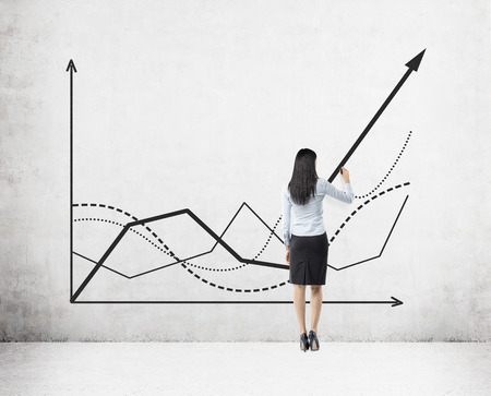 Rear view of businesswoman in skirt drawing a growing graph on concrete wall. Concept of statistician's work Foto de archivo