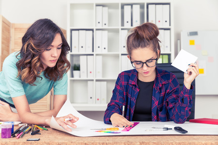 Two women are working together making a scheme on a large sheet of paper. Concept of project work