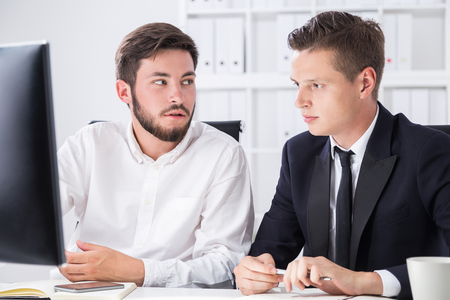 webmaster website: Two partners sit at computer desk  in office and talk about current company position on market. Concept of business planning Stock Photo