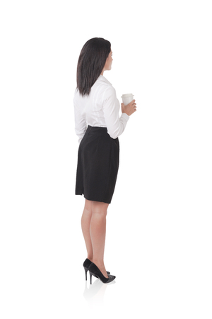face off: Isolated side view of businesswoman with paper cup of coffee standing with her face off the camera against white background and wearing black skirt and white shirt. Concept of business person Stock Photo