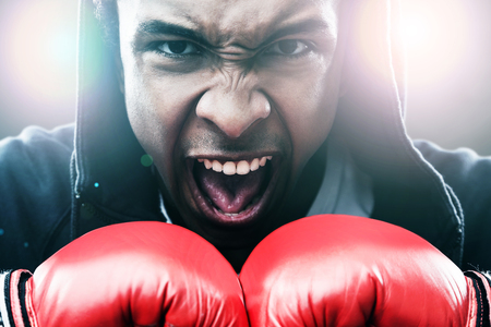 enraged: Close up of enraged African American man in boxing gloves. Concept of championship