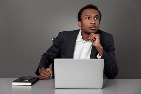 paz interior: Soñadora hombre de negocios estadounidense está contemplando en su lugar de trabajo. Concepto de la búsqueda de la paz interior Foto de archivo