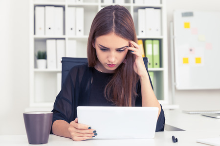 personal digital assistant: Serious girl in black is looking at her tablet computer screen. Concept of perfectionism at work and everyday life