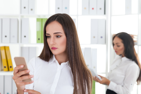 face centered: Portrait of serious businesswoman looking at her phone screen. Her colleague is reading in the background. Concept of office life