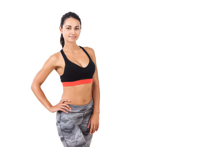staying fit: Portrait of fitness coach wearing sport bra and sweatpants and standing with her waist bent looking at the viewer with content expression. Concept of staying fit. Mock up
