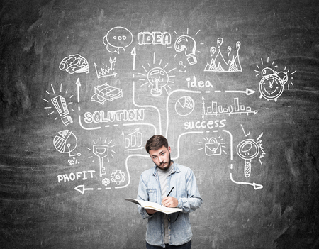 business it: Young engineer standing near blackboard with scientific startup sketch on it. Concept of business and science. Stock Photo