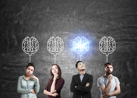 bocetos de personas: Group of people standing near chalkboard with brain sketches. One of them is shining. Concept of teamwork