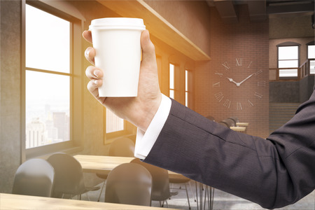 meet up: Sunlit coffee shop interior with huge clock on brick wall. Close up of mans hand holding paper cup of coffee. Concept of luxury establishment and meet up place. 3d rendering. Toned image
