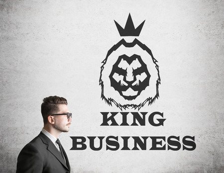 presumptuous: Side view of businessman in glasses with bad posture standing near concrete wall with king of business sketch on it. Concept of paying with your health for success