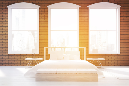 sunlit: Front view of sunlit bedroom with large clock on gray wall, massive bed and a table. Concept of cozy room. 3d rendering. Toned image Stock Photo