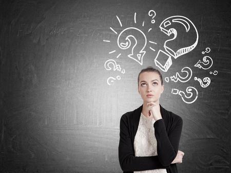黒のカーディガンに疑問符スケッチとともに黒板近くに立っている女の子を熟考します。あまりにも多くの質問の概念。モックアップします。 写真素材