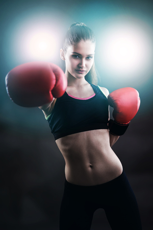 girl punch: Portrait of girl boxer in black sportswear making a punch and looking at the viewer. Concept of competition in sports
