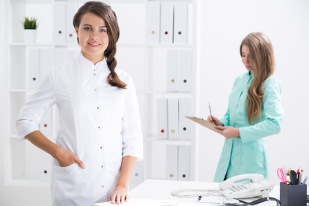 Smiling woman with braided hair is looking at the viewer. Her colleague in green gown is taking notes. Concept of medical office routine Stock Photo