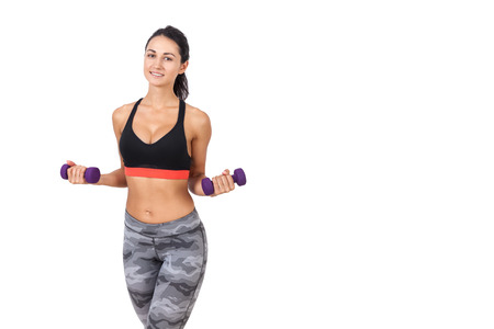 staying fit: Front view of lovely young lady with purple dumbbells making an exercise. Concept of working out and staying fit. Mock up Stock Photo