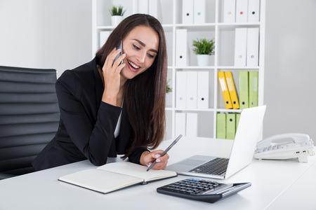 amigas conversando: Mujer sonriente en negro está hablando con su novia en el teléfono durante la hora del almuerzo en el trabajo. Concepto de conversación amistosa Foto de archivo