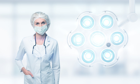 operation theatre: Portrait of woman surgeon standing in mask and cloak near a large operation theatre lamp pointed at the viewer. Concept of surgery Stock Photo