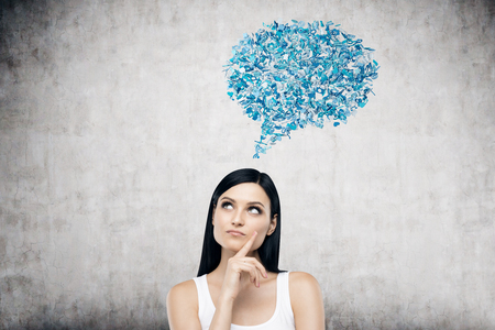 Portrait of girl with black hair standing near concrete wall with blue speech bubble near her head. Concept of call expressing your opinion. Mockup Stock Photo