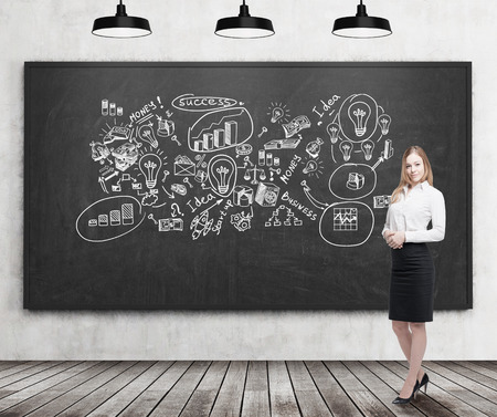 statistician: Smiling blond businesswoman standing near blackboard with business ideas on it. Concept of creativity in business Stock Photo