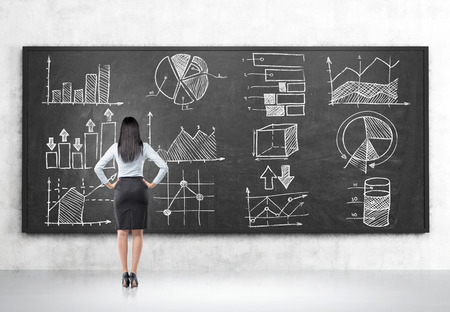 statistician: Rear view of girl looking at graphs on blackboard in room with concrete walls and floor. Concept of statistics in business management