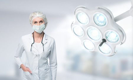 surgical mask woman: Woman doctor in surgical mask standing near operation room lamp looking down against blurred background. Concept of operation Stock Photo