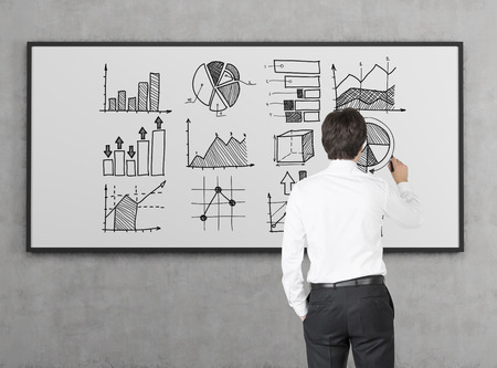 statistician: Rear view of businessman in white shirt drawing graphs on whiteboard. Concept of stats and big data Stock Photo