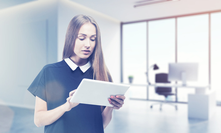 personal digital assistant: Beautiful blond girl in black dress is standing with her tablet in office and looking at the screen. Concept of good secretary. 3d rendering. Mock up. Toned image Stock Photo