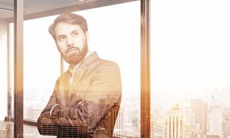 lit image: Bearded businessman dreaming about elimination of his competitioners in his large city apartment lit by sun. Toned image. Double exposure