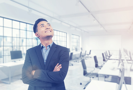 Portrait of successful Asian manager standing in his office with computer and panoramic windows. Concept of excellent career. 3d rendering. Mock up