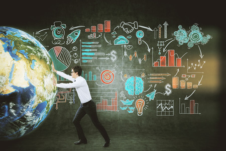 green arrow: Side view of young businessman pushing the globe against blackboard with startup images. Concept of international business. Toned image Stock Photo