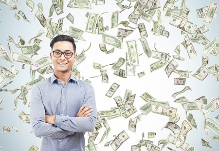Happy Asian man in glasses standing under dollar bill rain. Concept of successful business. Mockup