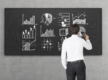 statistician: Rear view of businessman in white shirt drawing graphs on blackboard. Concept of stats and big data