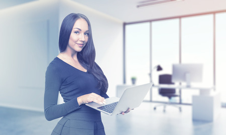 viewer: Beautiful girl in black dress is standing with her laptop in office and looking at the viewer. Concept of good secretary. 3d rendering. Mock up. Toned image