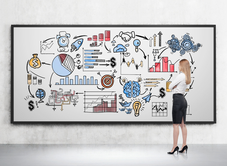 business gears: Side view of blond girl drawing icons on whiteboard in room with concrete walls and floor. Concept of business