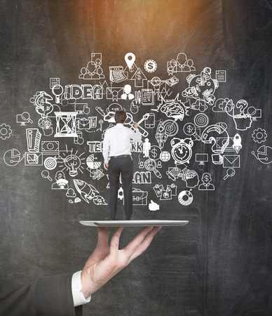 creative idea: Rear view of miniature businessman drawing startup sketch on chalkboard while standing on tray held by a giant. Concept of common person doing all work. Mock up. Toned image