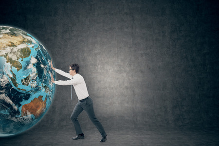 business globe: Side view of young businessman pushing the globe against blackboard . Concept of a fresh start in business. Toned image. Mock up Stock Photo