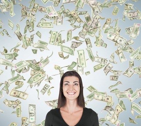 sudden: Smiling girl standing under dollar rain against light gray wall background. Concept of sudden money acquisition