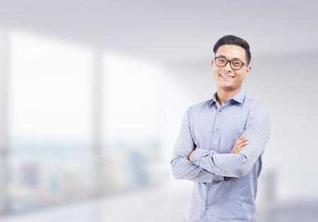 メガネの腕の側に立っての笑みを浮かべてアジア ビジネスマンは背景にぼやけオフィス折り返されている.成功した起業家のコンセプトです。モック