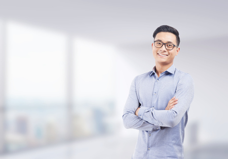 Smiling Asian businessman in glasses standing with arms folded against blurred office background. Concept of successful startup founder. Mock up Stock Photo