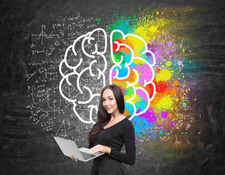 creatively: Portrait of girl with notebook standing near blackboard with giant brain sketch and formulas. Concept of thinking creatively