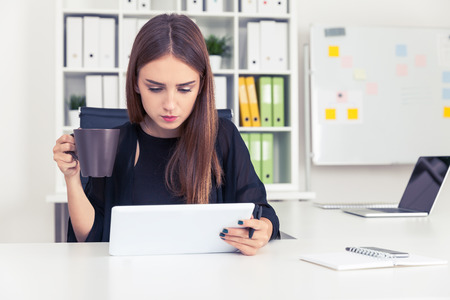 personal digital assistant: Centered businesswoman is looking at her laptop screen and drinking coffee from brown mug. Concept of morning in the office