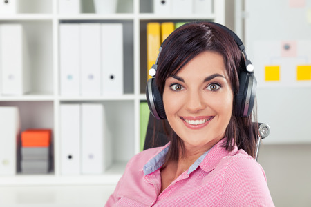 hedonism: Cheerful office employee in pink shirt is listening to energetic music at work during her lunch break. Concept of hedonism