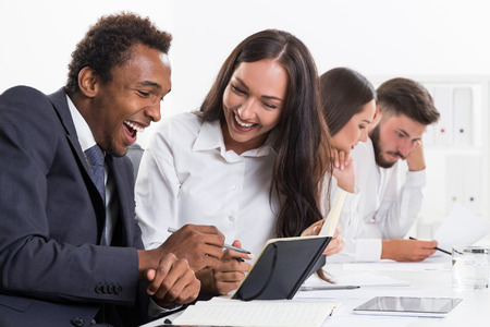 discovered: Colleagues are laughing because they have just discovered some new approach to business. Their coworkers are sad because they didnt Stock Photo
