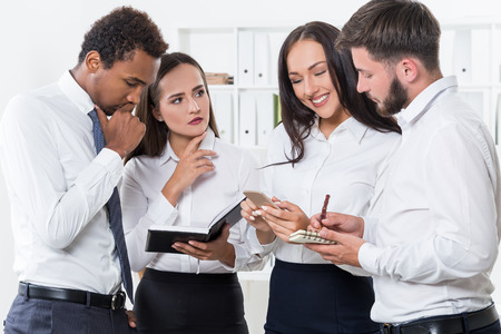 professionalism: Group of businesspeople discussing tough problem. One girl is cheerfully checking her phone. They question her professionalism Stock Photo