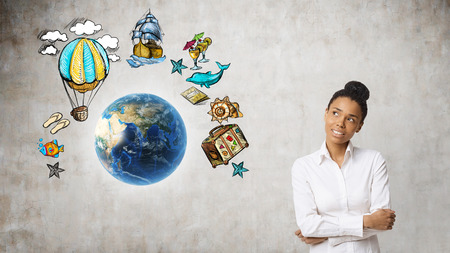 Smiling African American girl standing near planet Earth surrounded by travelling sketches. Concept of seeing the world.