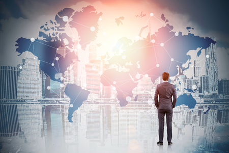 Rear view of businessman in suit looking at city panorama. Map of the world in the sky. Continents are marked with dots. Toned image. Double exposure. Stock Photo
