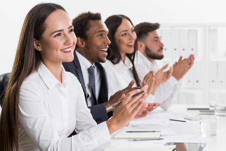 aplaudiendo: Group of colleagues applauding to some person off camera while sitting at the office. Concept of recognition and approval Foto de archivo